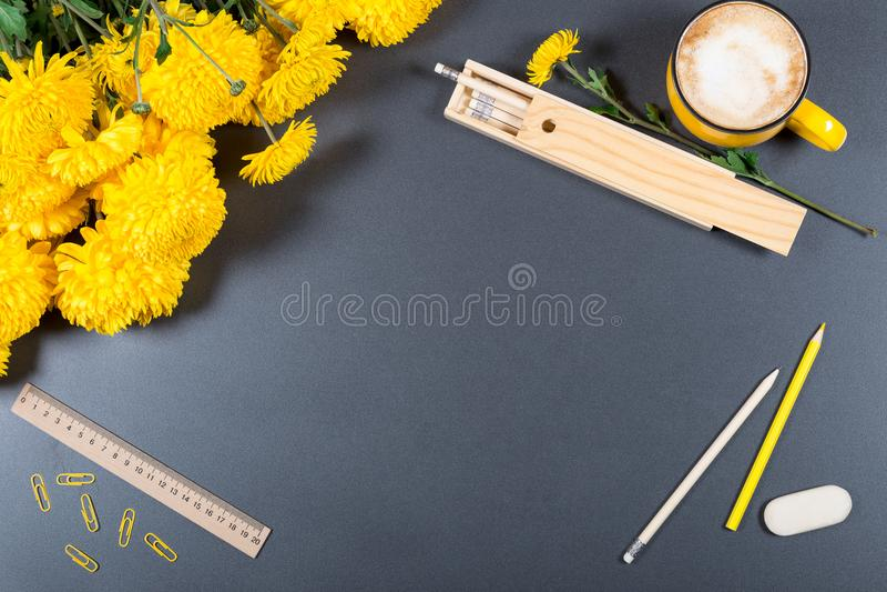与颜色铅笔、橡皮擦、统治者、木铅笔盒、大杯子热奶咖啡和束的灰色书桌表面黄色菊花 免版税库存图片