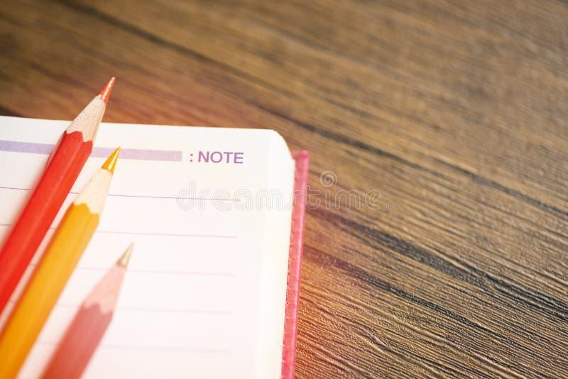 与颜色铅笔的笔记薄或笔记本纸在桌教育和回到学校概念 图库摄影