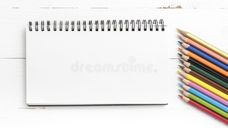 与颜色铅笔的笔记薄 免版税库存图片
