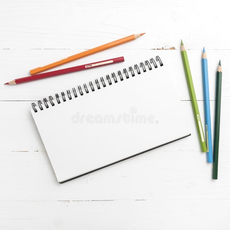 与颜色铅笔的笔记薄 库存图片