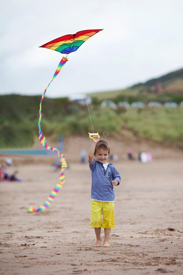 与风筝的微笑的孩子,走在海滩 库存图片
