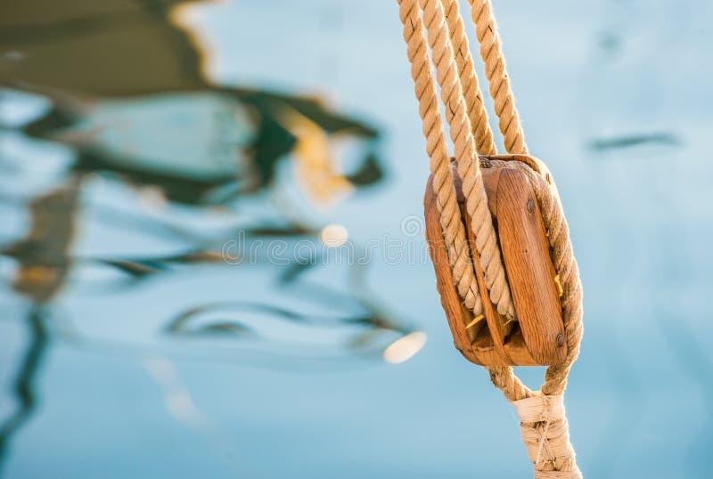 与风船滑轮、滑车和船舶块的乘快艇的船舶背景 免版税库存图片