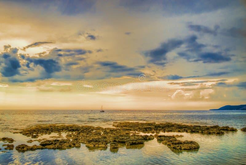 与风船的在黄昏的海边和岩石 库存图片