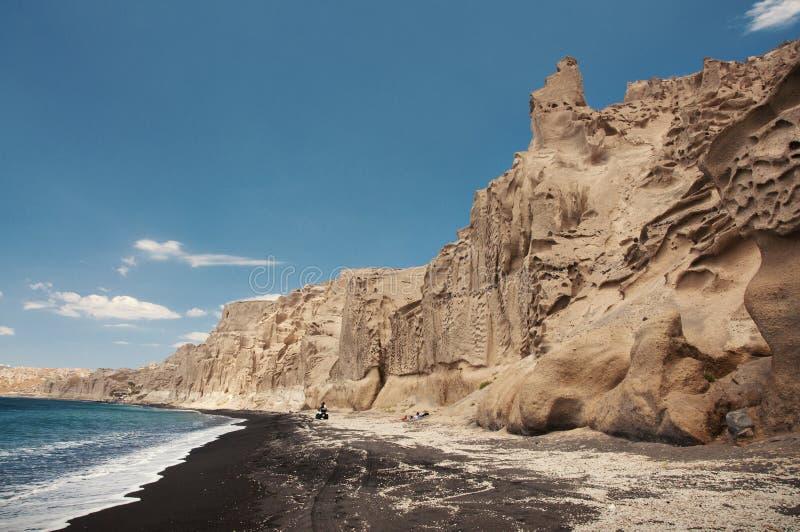 与风被雕刻的峭壁的黑沙子海滩 库存图片