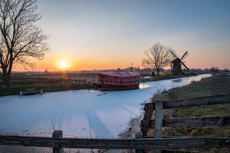 与风车的冬天场面在日落的荷兰 库存图片
