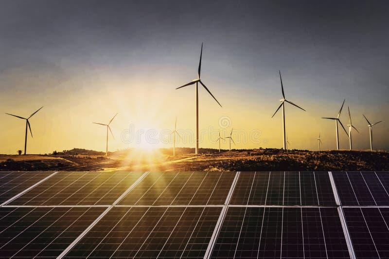 与风轮机和日落的太阳电池板 概念力量能量 免版税库存照片