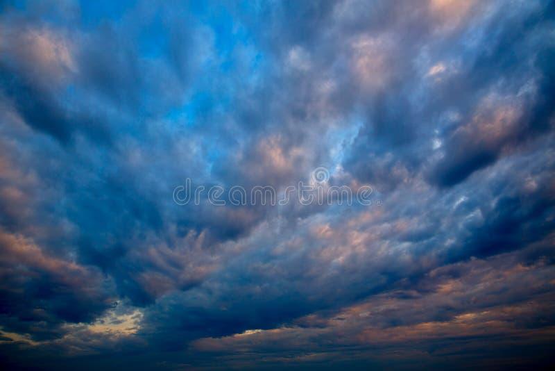 与风雨如磐的云彩的剧烈的天空在日落 库存照片