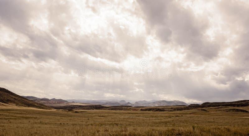 与风雨如磐的天空和落矶山的西部平原风景 库存照片