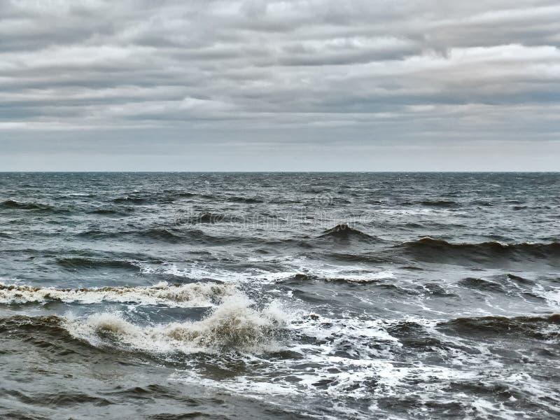 与风雨如磐的波浪和灰色云彩的黑暗的沉思的海景 库存图片