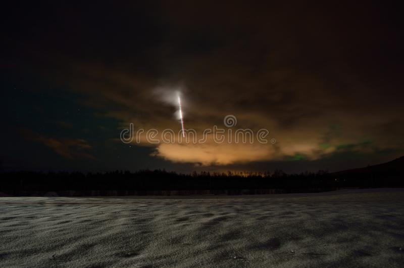 与飞机光和极光borealis的长的冬天领域在夜空 免版税库存照片