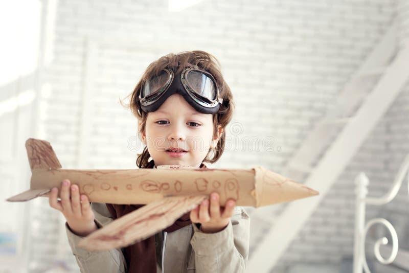 与飞机的愉快的男孩戏剧在手中,孩子作梦关于traveli 图库摄影