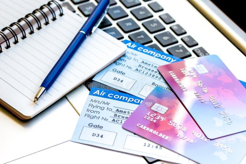 与飞机票的信用卡在膝上型计算机背景的假期 库存照片
