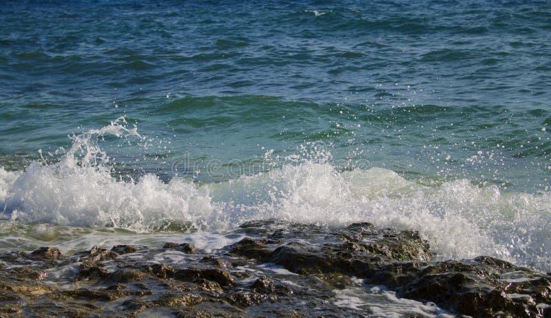 与飞溅在海滩岩石的白色波浪的蓝色海视图 在大浪期间的火山的海边 免版税库存照片
