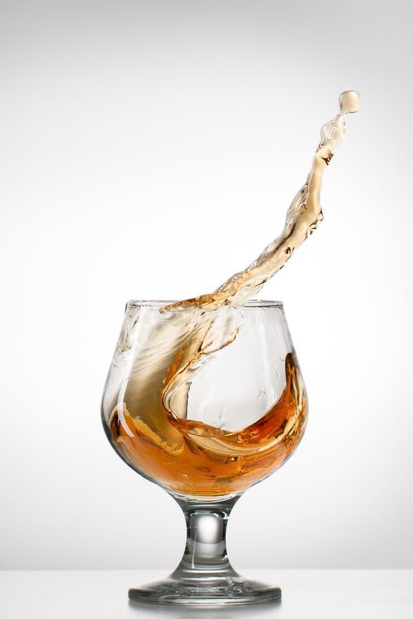 与飞溅的科涅克白兰地玻璃 免版税库存照片