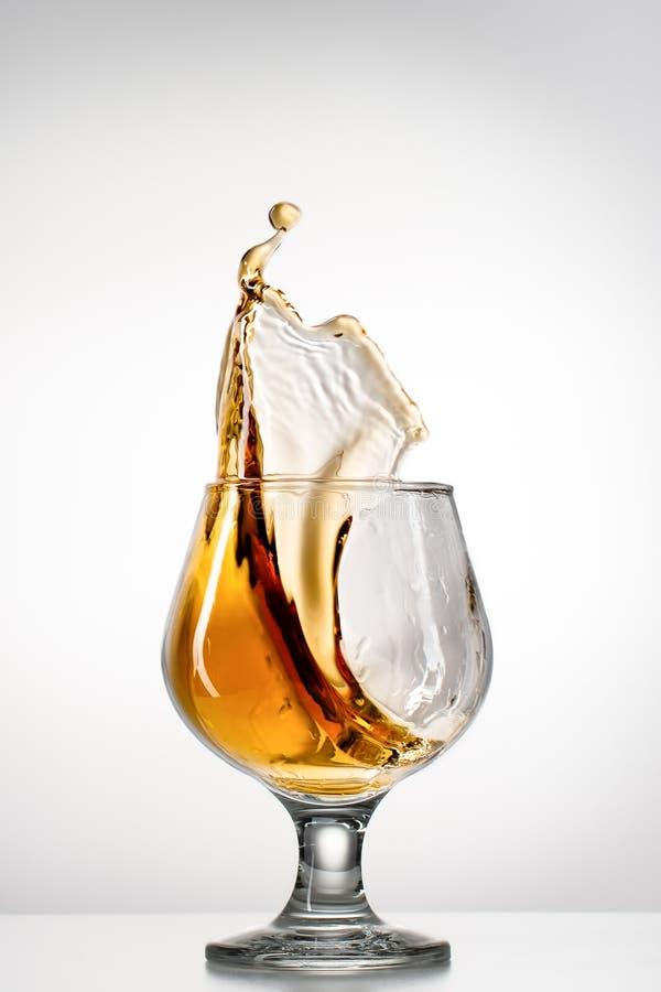 与飞溅的科涅克白兰地玻璃 免版税库存图片