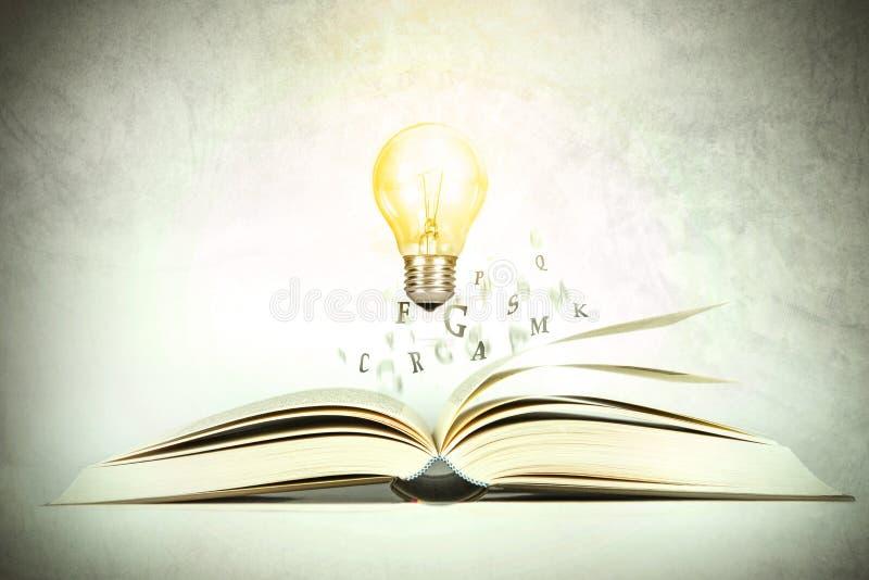 与飞行与发光的lig的字母表信件的被打开的书 免版税库存照片
