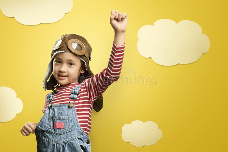 与飞行员帽子的快乐的亚洲获得孩子和的风镜乐趣 库存照片