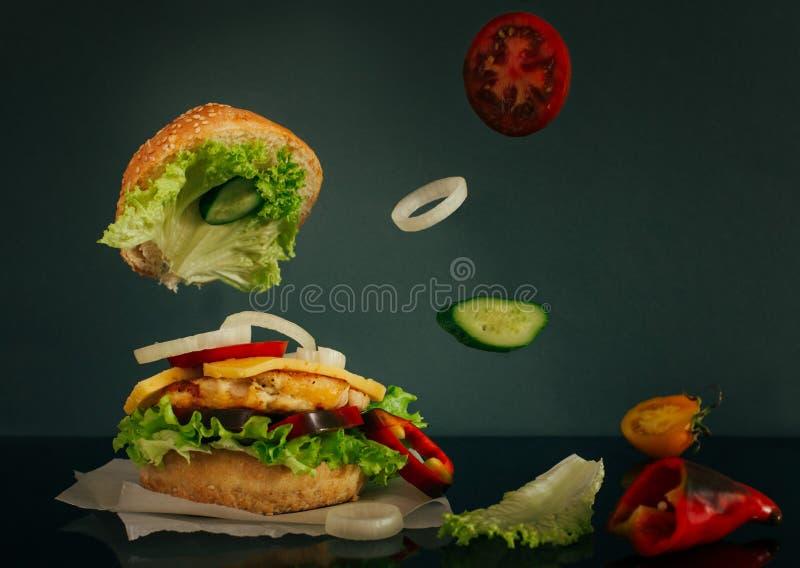 与飞行成份的可口汉堡在黑暗的背景 图库摄影
