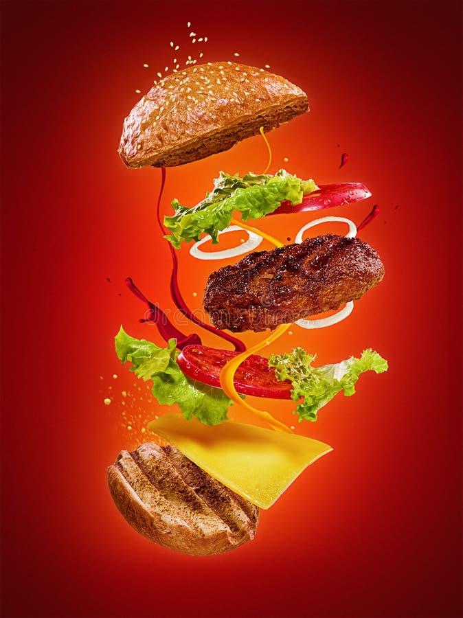 与飞行成份的汉堡包在红色背景 免版税库存照片