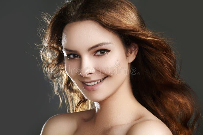 与飞行棕色头发的美好的少妇模型 与干净的皮肤的秀丽,时尚构成 组成,卷曲发型 免版税库存照片