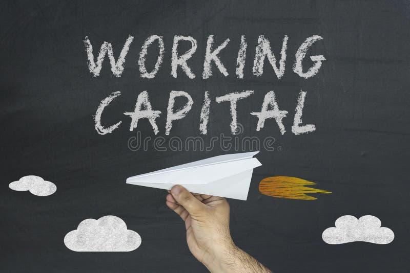 与飞行纸飞机的周转资本概念在黑板 免版税库存图片