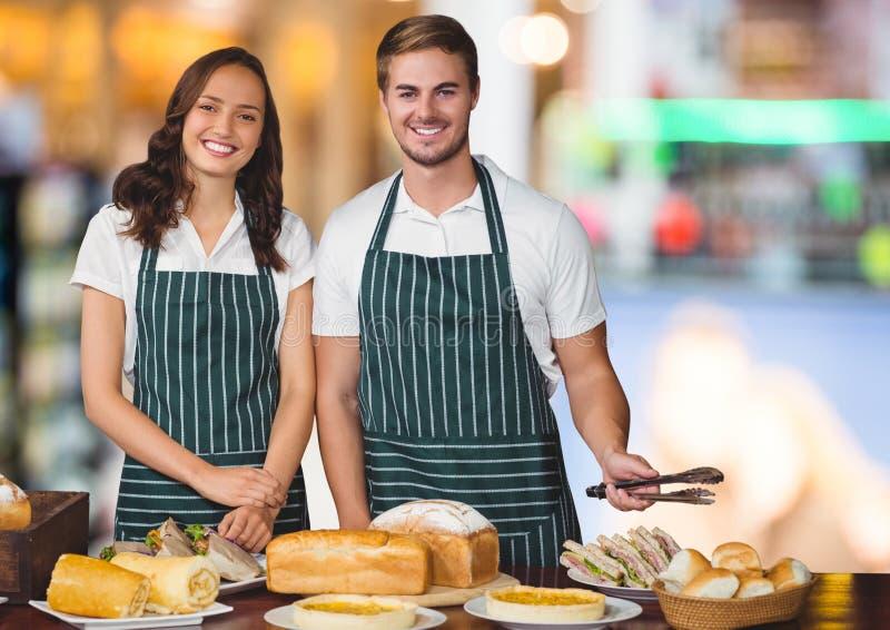 与食物桌的面包店所有者反对模糊的背景 免版税库存照片