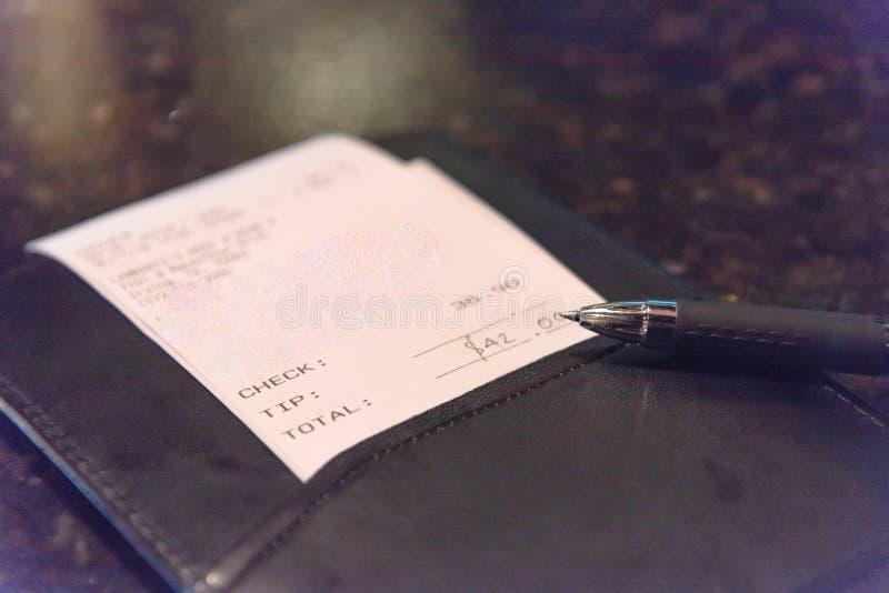 与餐馆票据检查和笔的特写镜头皮革持有人 库存照片