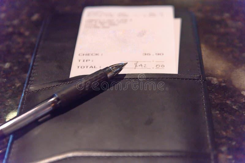 与餐馆票据检查和笔的特写镜头皮革持有人 免版税库存照片