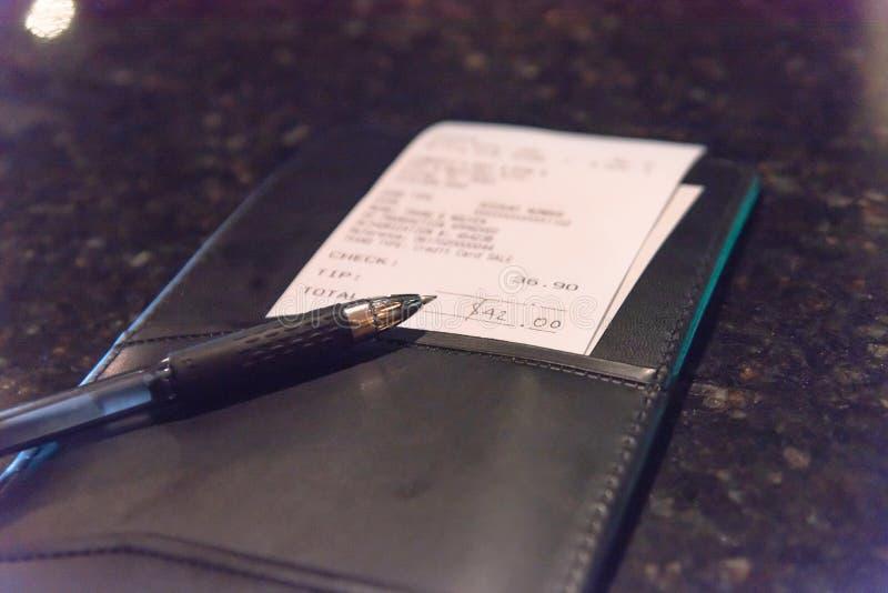 与餐馆票据检查和笔的特写镜头皮革持有人 免版税库存图片
