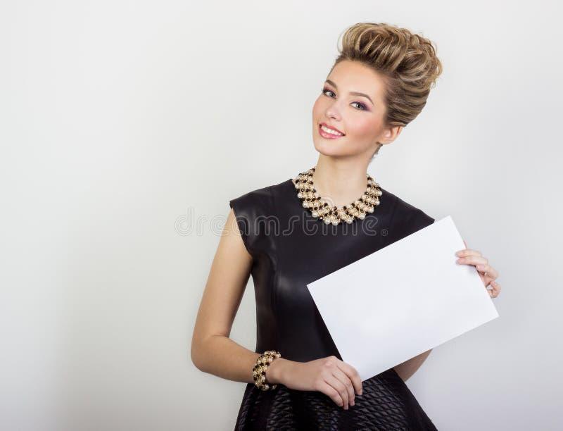 与首饰的少妇微笑在与头发的一件黑晚礼服的美丽的愉快的性感的和构成白色签到他的手 图库摄影
