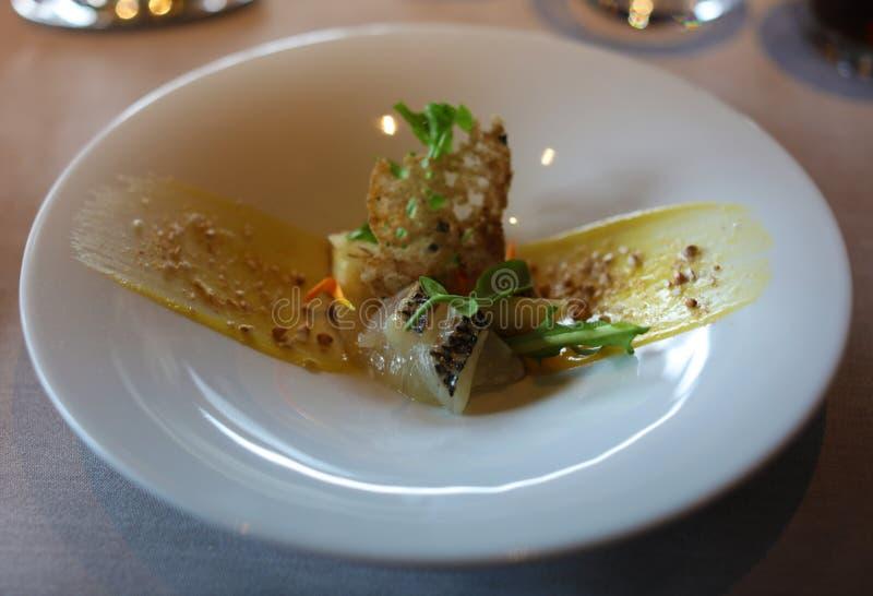 与香柠檬和柠檬sause,豪华膳食独特的烹调的用卤汁泡的海鲷在VIP美食术餐馆 库存图片