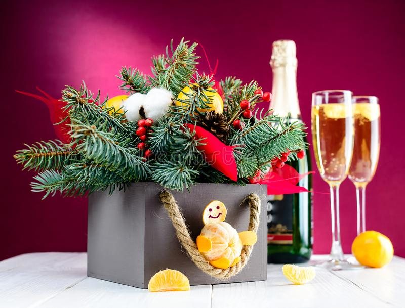 与香槟和圣诞节装饰箱子的玻璃反对桃红色 免版税库存图片