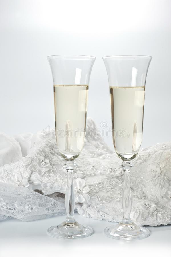 与香槟和婚礼礼服的玻璃在白色背景 免版税库存图片