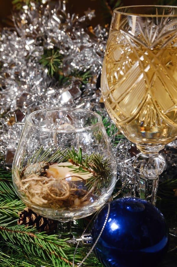 与香槟玻璃的一张装饰的圣诞节餐桌和圣诞树在背景中 免版税库存照片