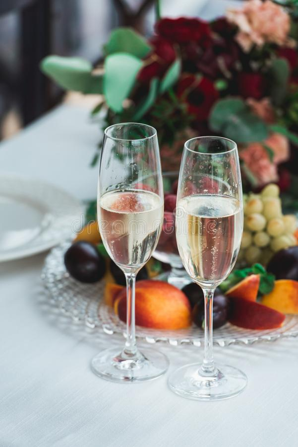 与香槟饮料的玻璃在桌上 愉快新婚佳偶喝 爱恋的夫妇创建了新的家庭 库存照片