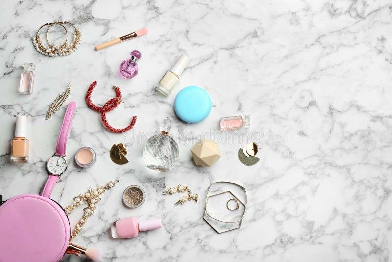 与香水瓶、首饰和装饰化妆用品的平的被放置的构成在白色大理石桌上 免版税图库摄影