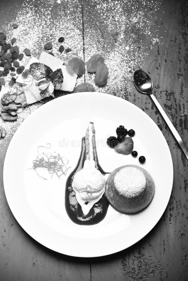 与香草冰淇淋的白色巧克力方旦糖和草莓在灰色背景调味 点心供食用干果 库存图片