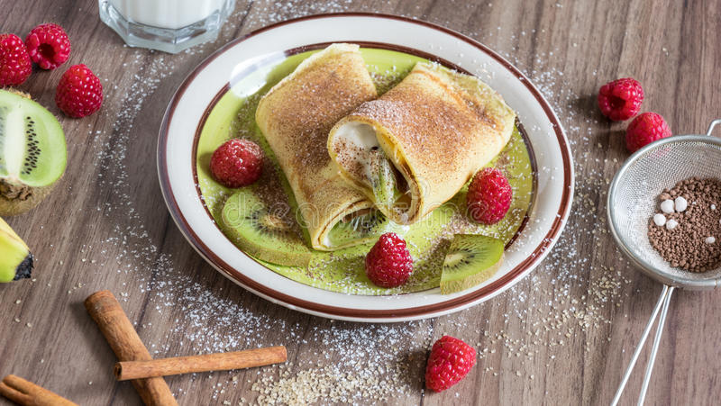 与香草凝乳、莓、猕猴桃和香蕉片的自创薄煎饼洒与可可粉 免版税库存照片
