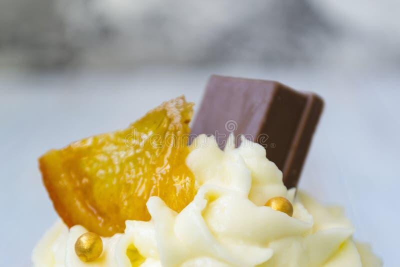 与香草黄油结霜的巧克力杯形蛋糕和金黄面包屑、巧克力和柠檬 有文本的一个备忘录 免版税库存图片