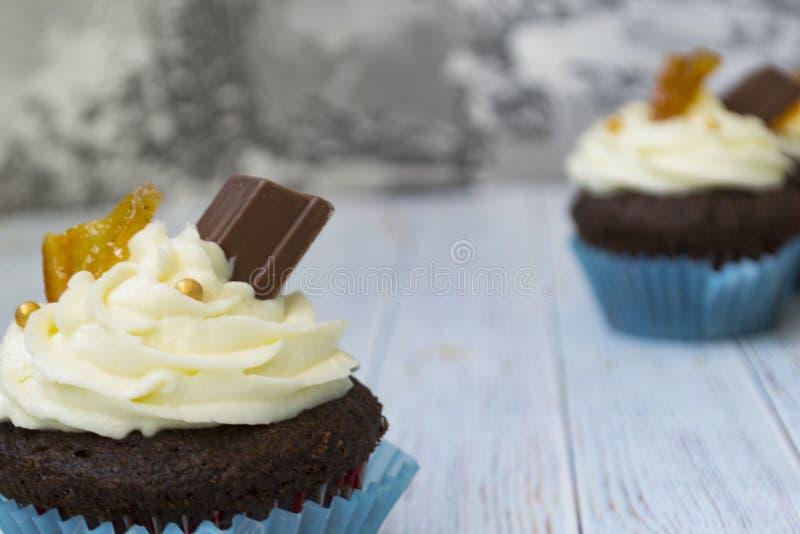 与香草黄油结霜的巧克力杯形蛋糕和金黄面包屑、巧克力和柠檬 有文本的一个备忘录 免版税库存照片