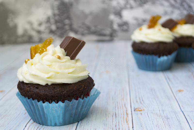 与香草黄油结霜的巧克力杯形蛋糕和金黄面包屑、巧克力和柠檬 有文本的一个备忘录 图库摄影