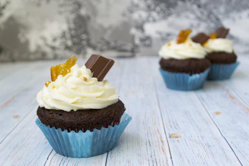 与香草黄油结霜的巧克力杯形蛋糕和金黄面包屑、巧克力和柠檬 有文本的一个备忘录 库存照片