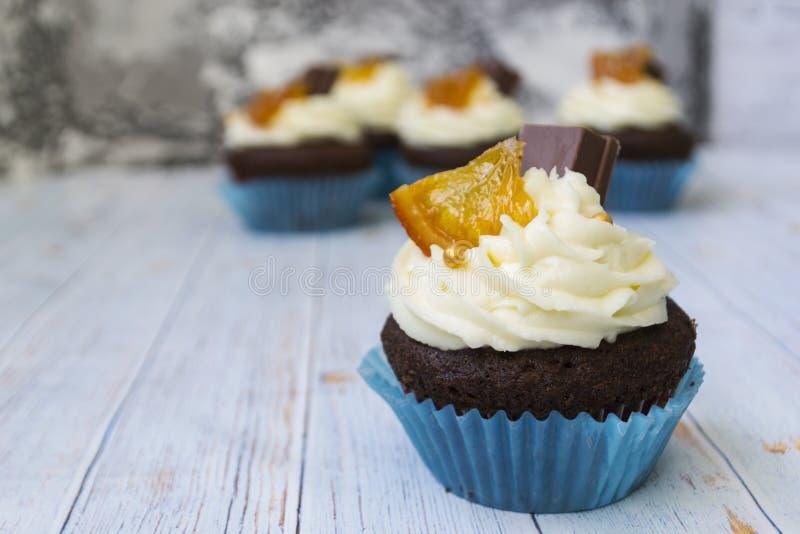 与香草黄油结霜的巧克力杯形蛋糕和金黄面包屑、巧克力和柠檬 有文本的一个备忘录 免版税图库摄影