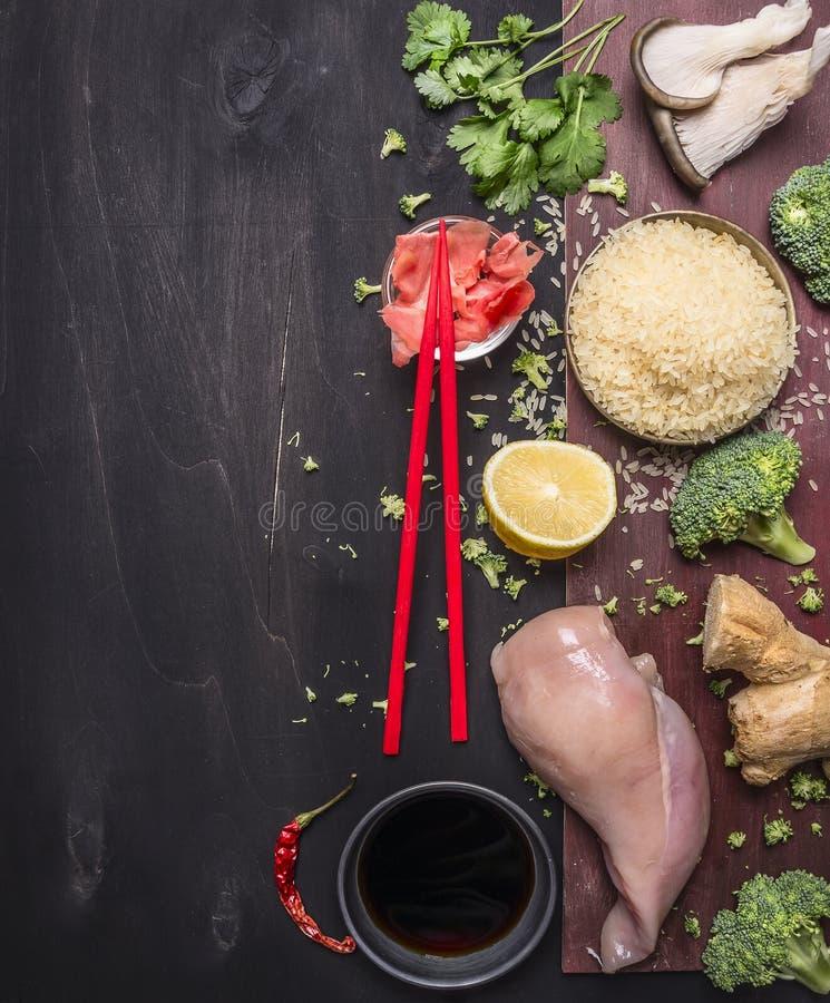 与香菜、姜、酱油、蚝蘑和柠檬,鸡胸脯,红色筷子,日本f的概念的未煮过的米 免版税图库摄影