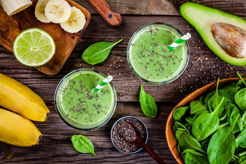 与香蕉、石灰、菠菜、鲕梨和chia种子的健康绿色圆滑的人在玻璃瓶子 免版税库存照片