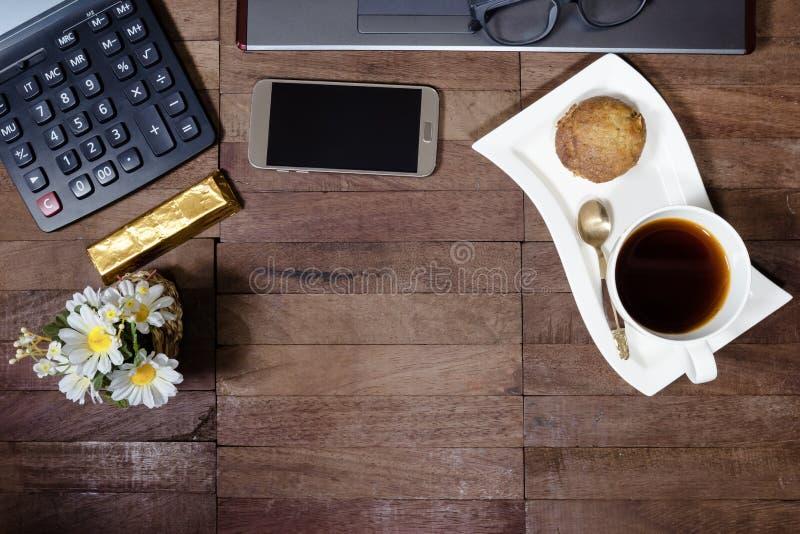 与香蕉杯子蛋糕和办公设备的咖啡在桌面上 免版税图库摄影