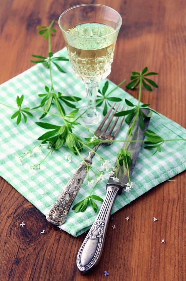 与香车叶草酒的玻璃在木桌上 免版税库存图片
