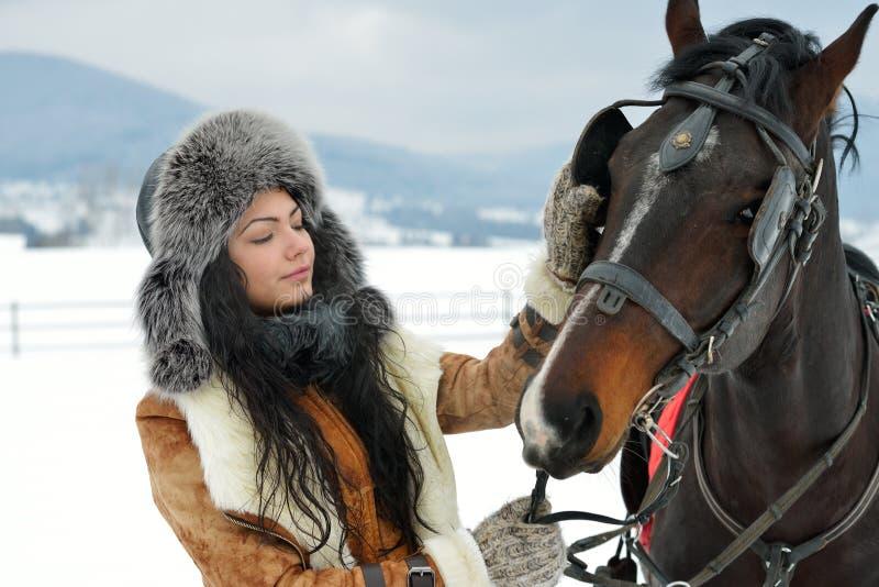 与马的美丽的深色的妇女画象在冬天 库存图片