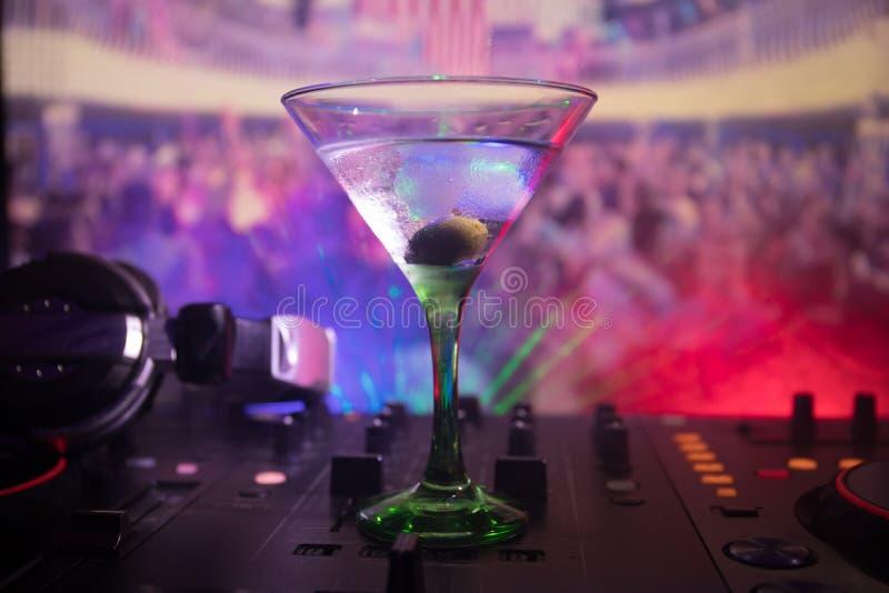 与马蒂尼鸡尾酒的玻璃用橄榄里面在夜总会的dj控制器 有俱乐部饮料的Dj控制台在音乐党在有d的夜总会 免版税库存图片