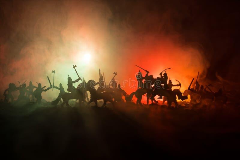 与骑兵和步兵的中世纪战斗场面 图剪影作为分开的对象,在战士之间的战斗被定调子的黑暗的 库存照片
